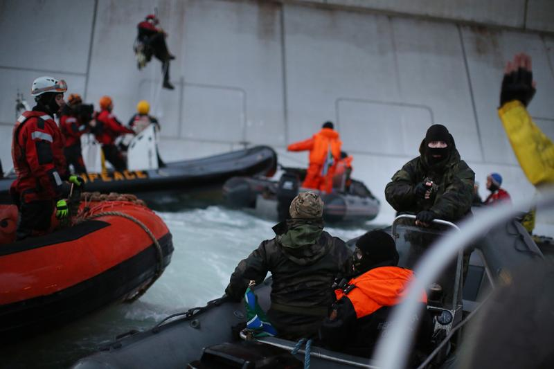 A Russian Coast guard officer is seen pointing a gun at a Greenpeace International activist as five activists attempt to climb the 'Prirazlomnaya,' an oil platform operated by Russian state-owned energy giant Gazprom platform in Russias Pechora Sea.  This is one example of the disproportionate use of force by the Russian authorities during a peaceful protest. The activists are there to stop it from becoming the first to produce oil from the ice-filled waters of the Arctic.